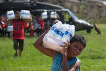 A young boy carries a case of water away from a helicopter in Puerto Rico
