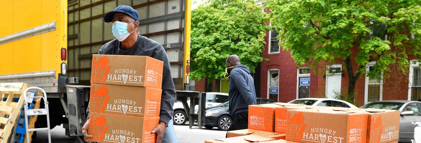 Men unload boxes of food from a truck